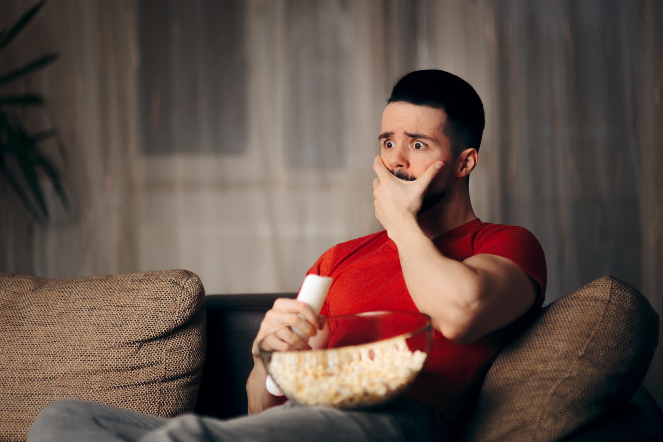 Young millennial guy spending free time binging on favorite show